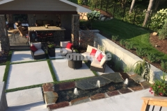 Bomanite Revealed Exposed Aggregate concrete was installed in this backyard space to create the steps, landing, and beautiful courtyard area, using inlays of grass to break up the expanse of concrete and add warmth to the space.
