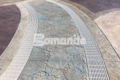This stunning hardscape at Canobie Lake Park was created using Bomanite Imprint Systems and our colleague, Harrington Bomanite, incorporated these serpentine drains into the design to infiltrate storm water and minimize runoff while accentuating the decorative concrete decking at the Castaway Island water feature.