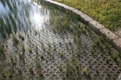 Grasscrete by Bomanite was installed here to create a pervious pavement system that is partially concealed with vegetation and was also integrally colored in an earthy brown tone to further blend in with the natural surroundings.